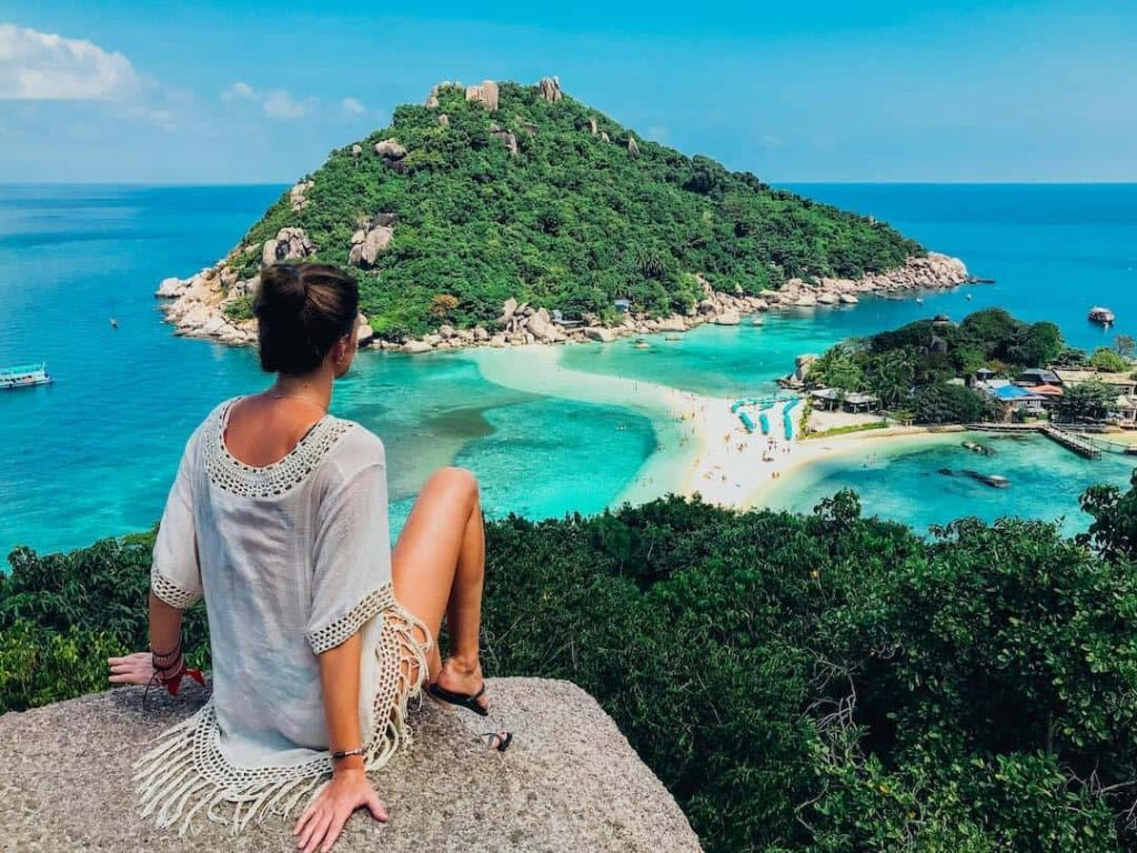 Woman sitting on a lookout point over the ocean in Thailand