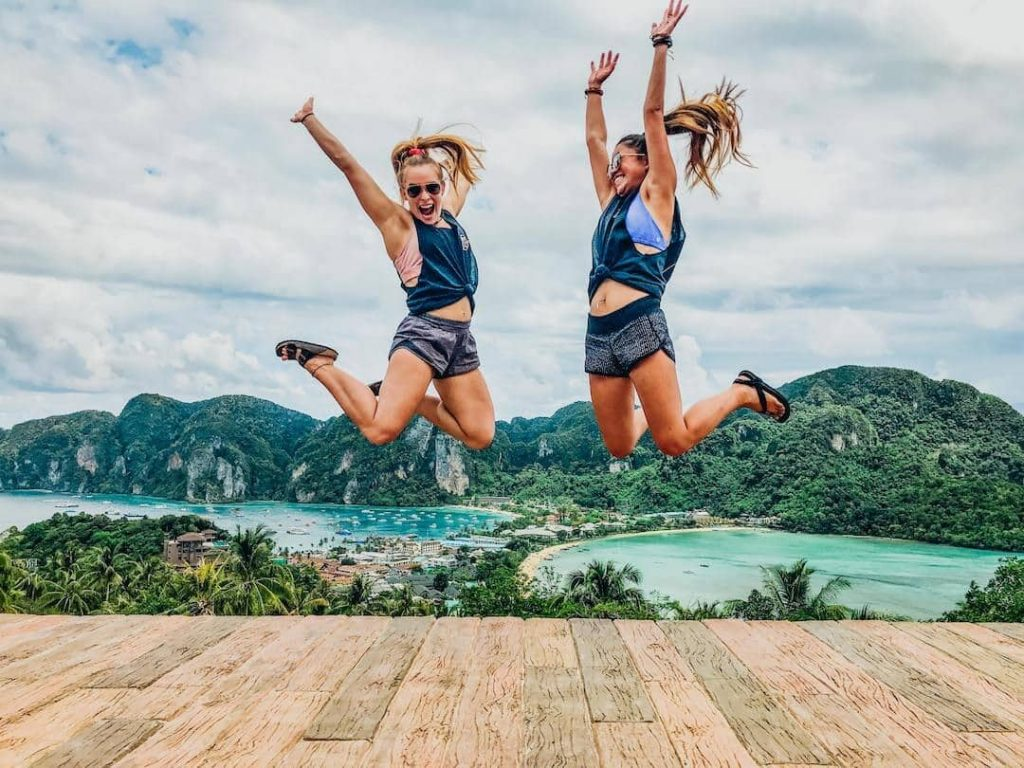 Two women jumping with a bay in the background in Thailand