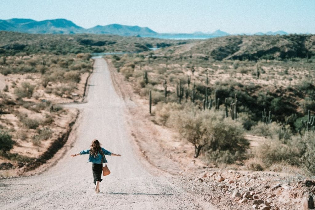 Woman running down a dirt road with cactus on either side and mountains in the distance