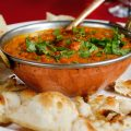 a dish of curry with naan