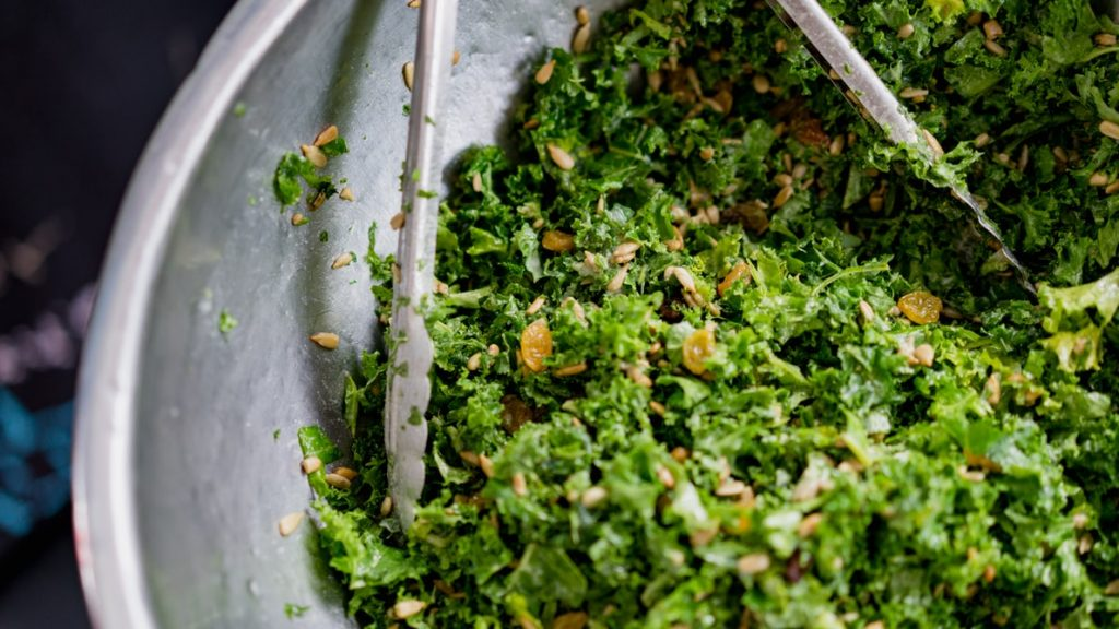 shredded greens and yellow raisins in a bowl