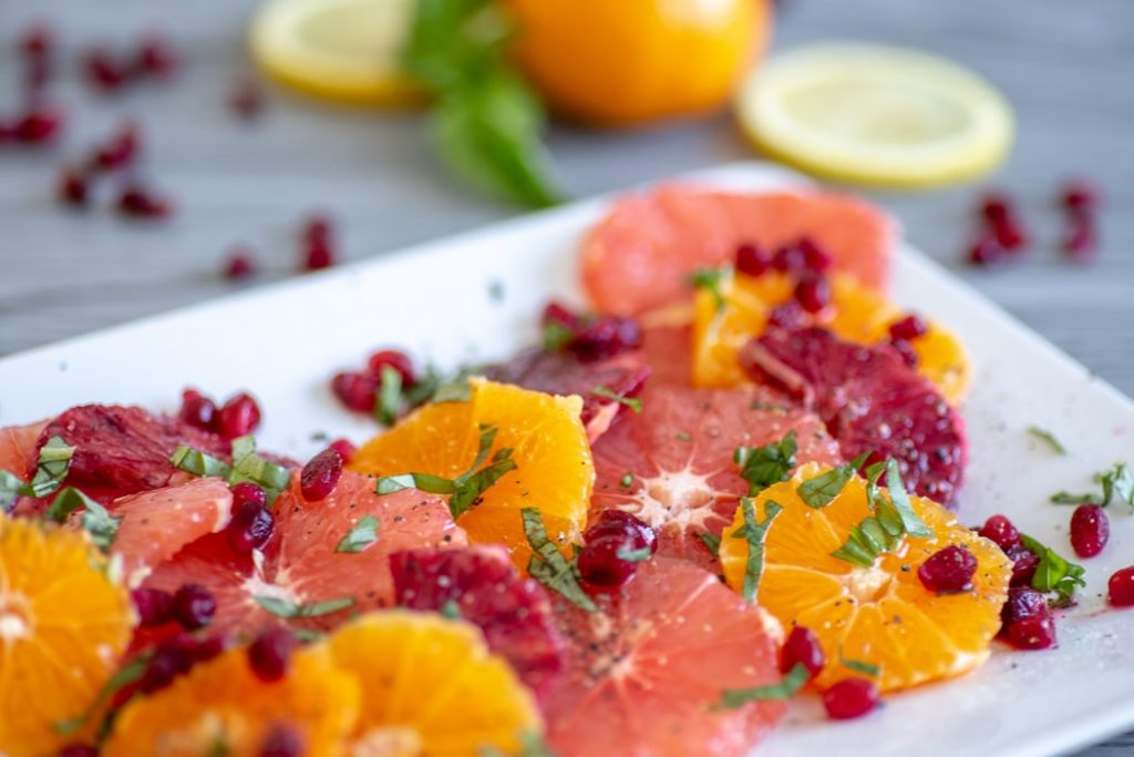 sliced oranges, coriander and pomegranate on a plate