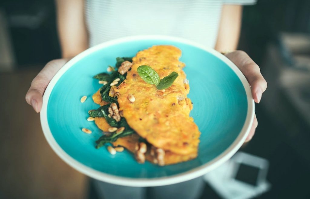 Woman holding a blue plate with an omelette