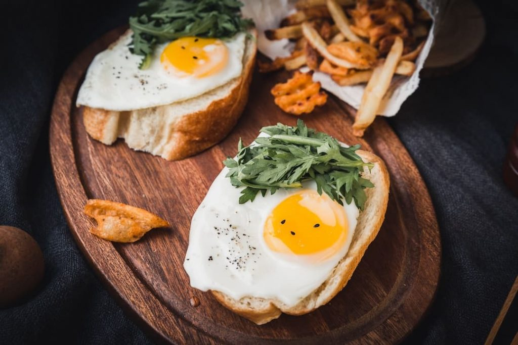 Two pieces of bread topped with a fried egg and french fries in the background