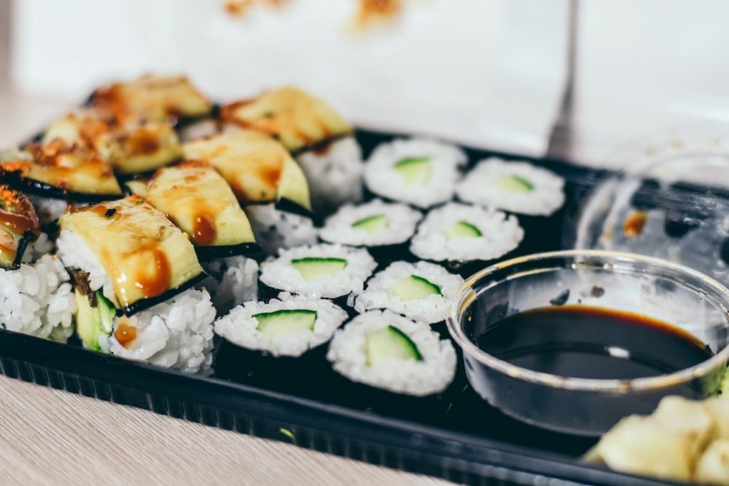 Take away sushi and soy sauce in a black container