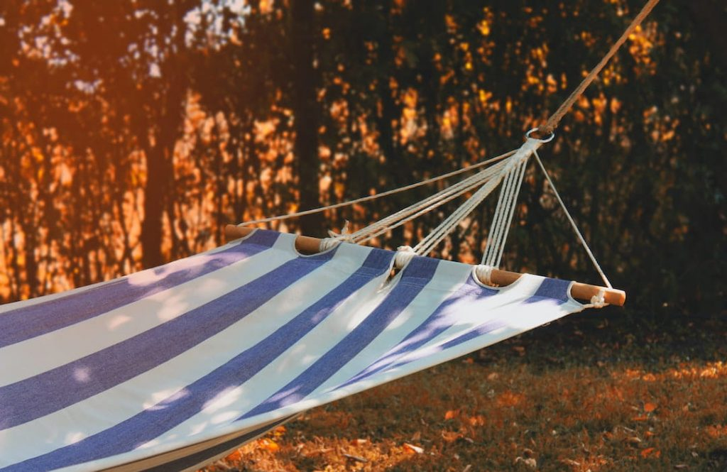 Blue and white striped hammock hanging in a yard