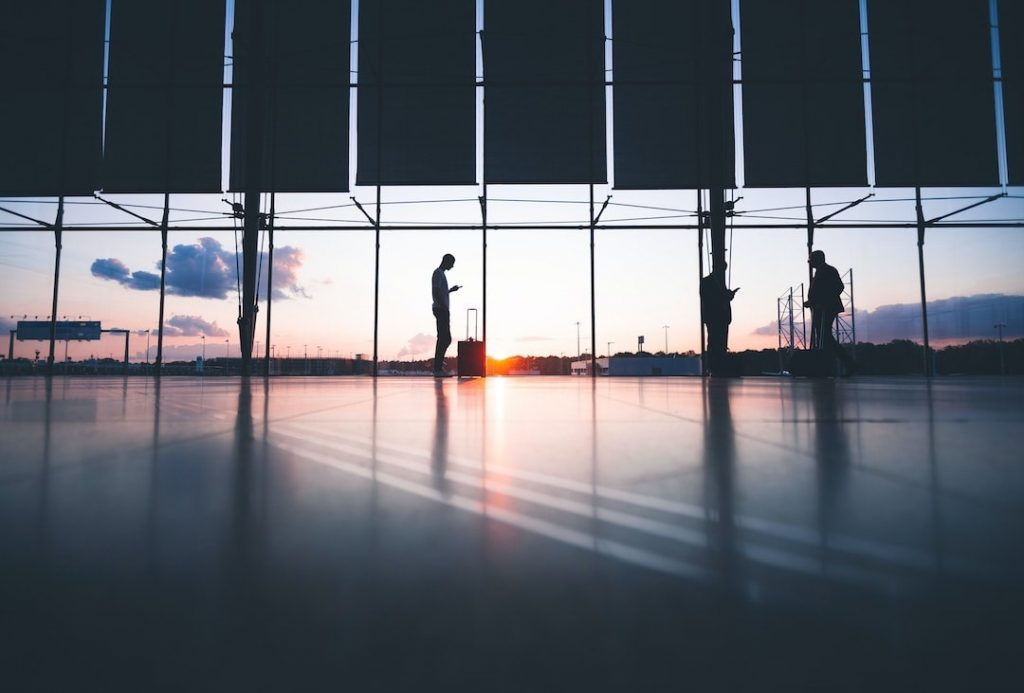 Three people standing in an empty airport terminal at sunrise