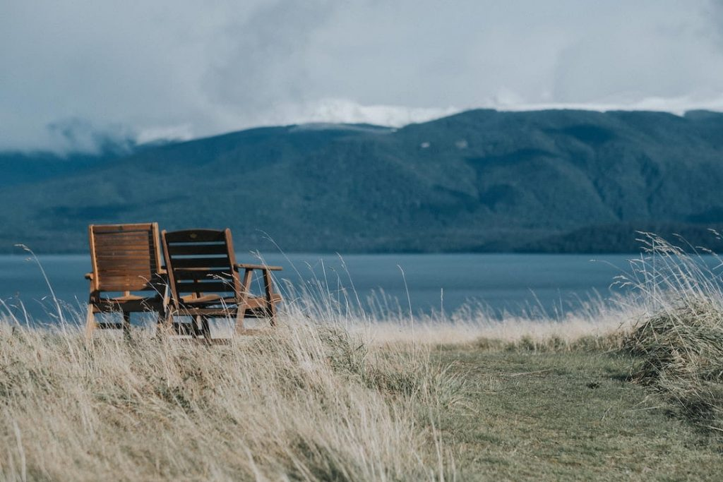 Two empty chairs beside a lake and long grass and hills