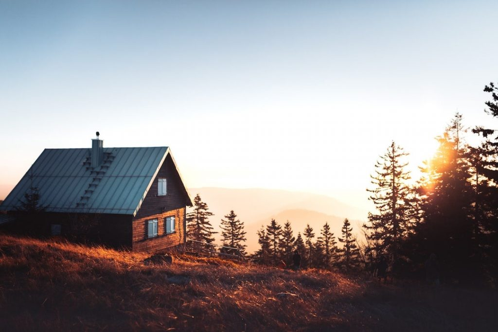 Small cabin surrounded by hills and trees