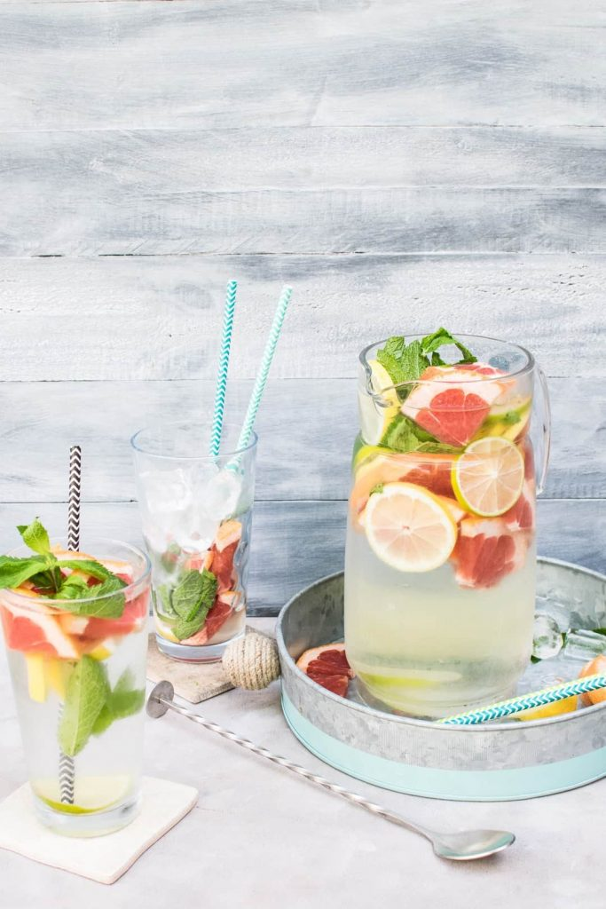 Water pitcher filled with water infused with citrus and mint