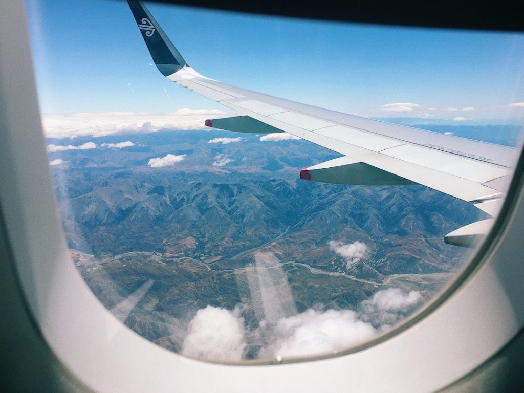 Airplane window with the view of the wing over mountains on Air New Zealand