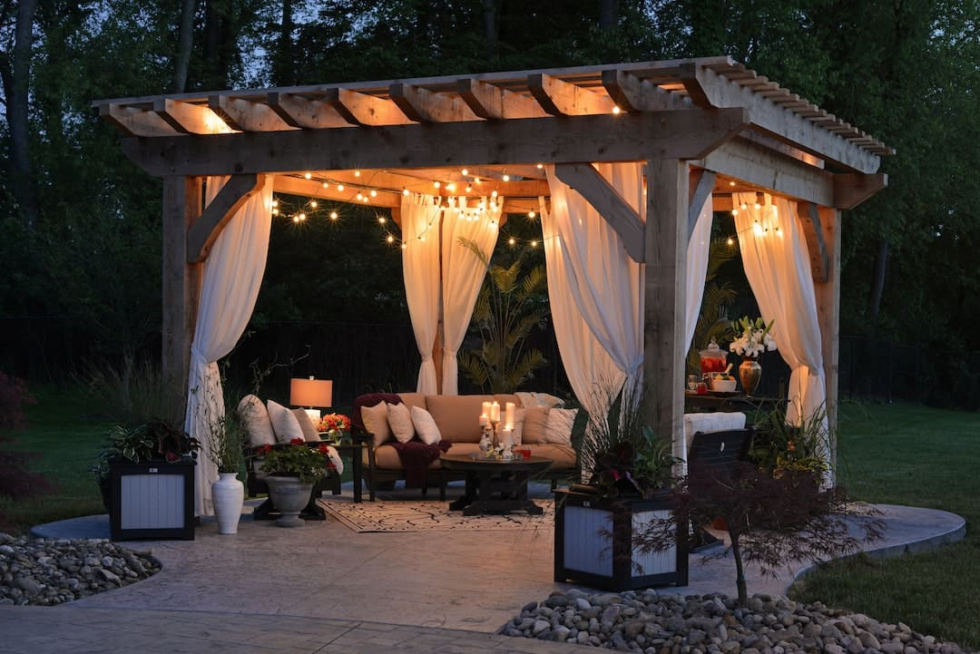 Outdoor furniture inside a gazebo with drapes and string lights