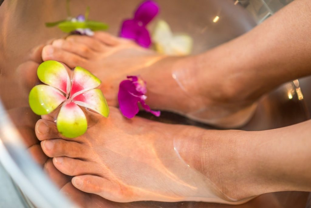 Feet soaking in a basin with flowers