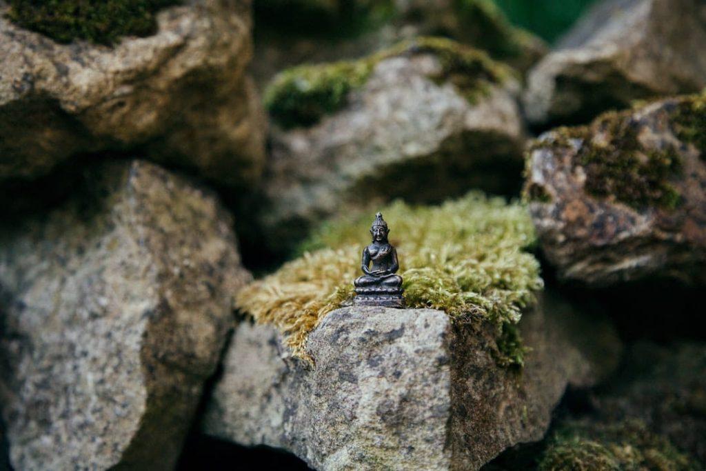 Tiny buddha statue sitting on moss-covered rocks