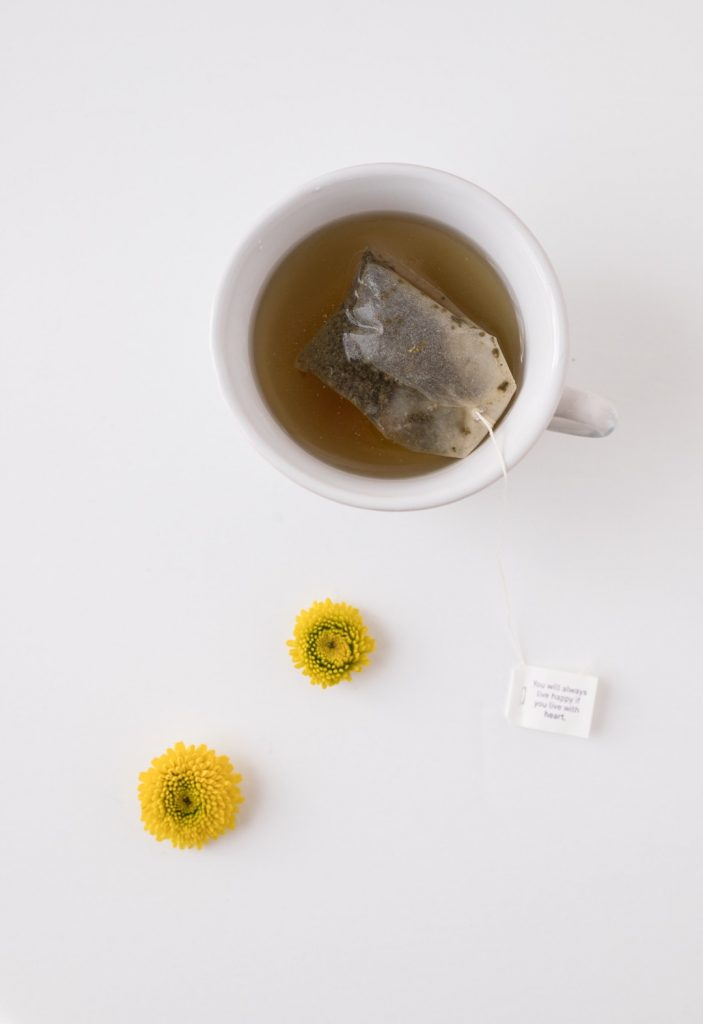 Cup of green tea with tag bag inside and two yellow flowers beside it