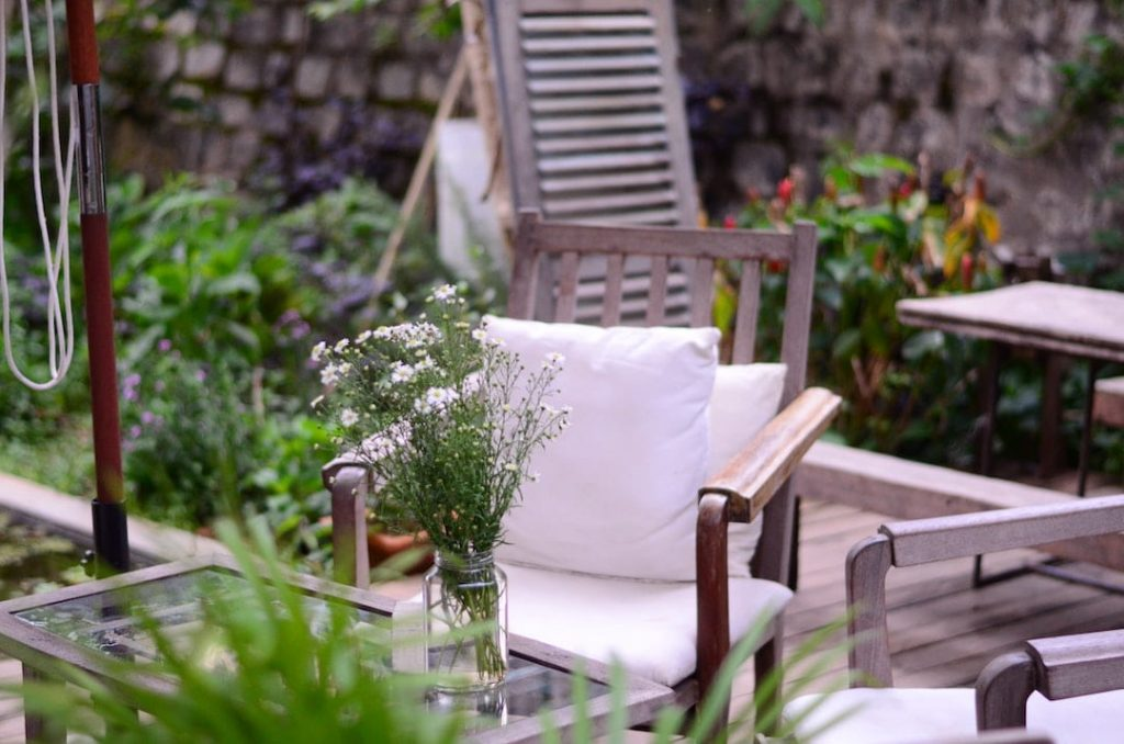Wooden chair with white cushions beside a vase of flowers in a yard