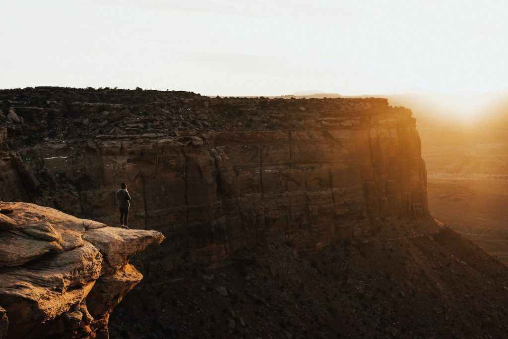 Woman standing on the edge of a cliff in Moab, United States
