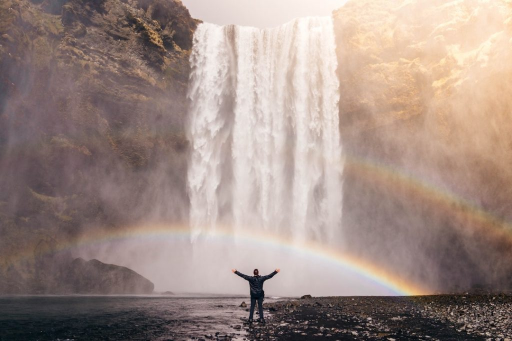 Person standing in front of waterfall and rainbow in Iceland