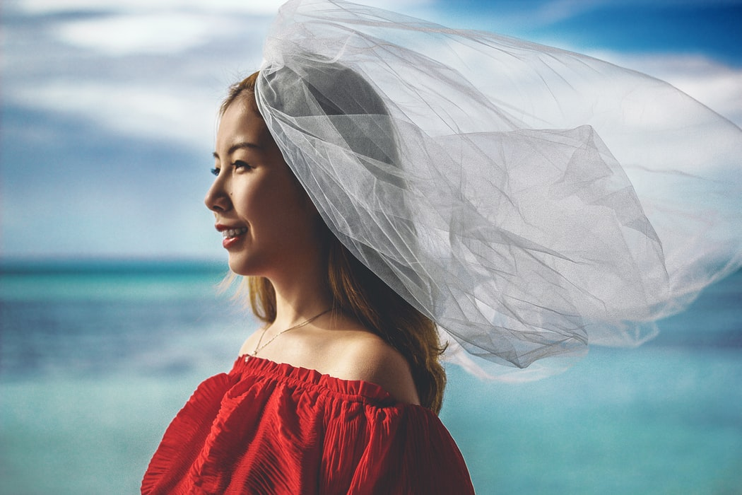a woman in a red dress and veil beside the sea