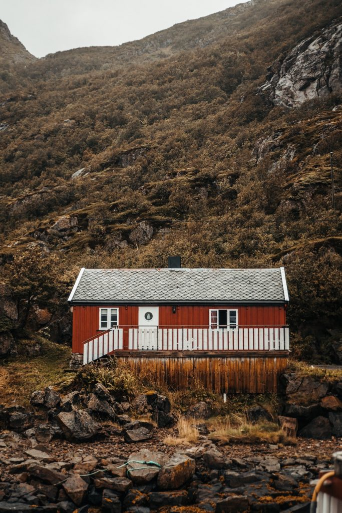 Red cabin surrounded by hills and rocks in Sweden