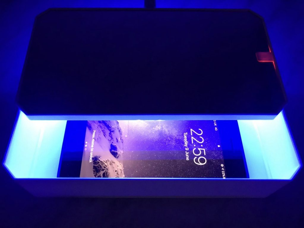 useful travel accessories: a box with a uv light in it cleaning a phone