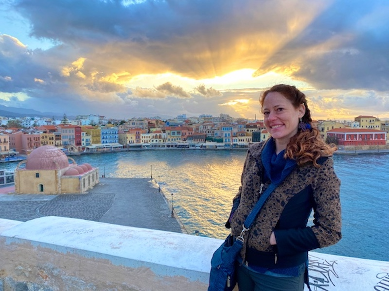 Woman standing in front of sunset in Chania, Greece