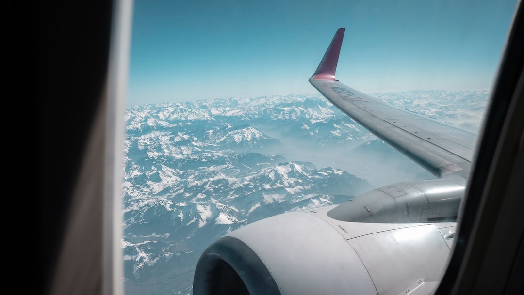 Airplane window view wing over mountain range