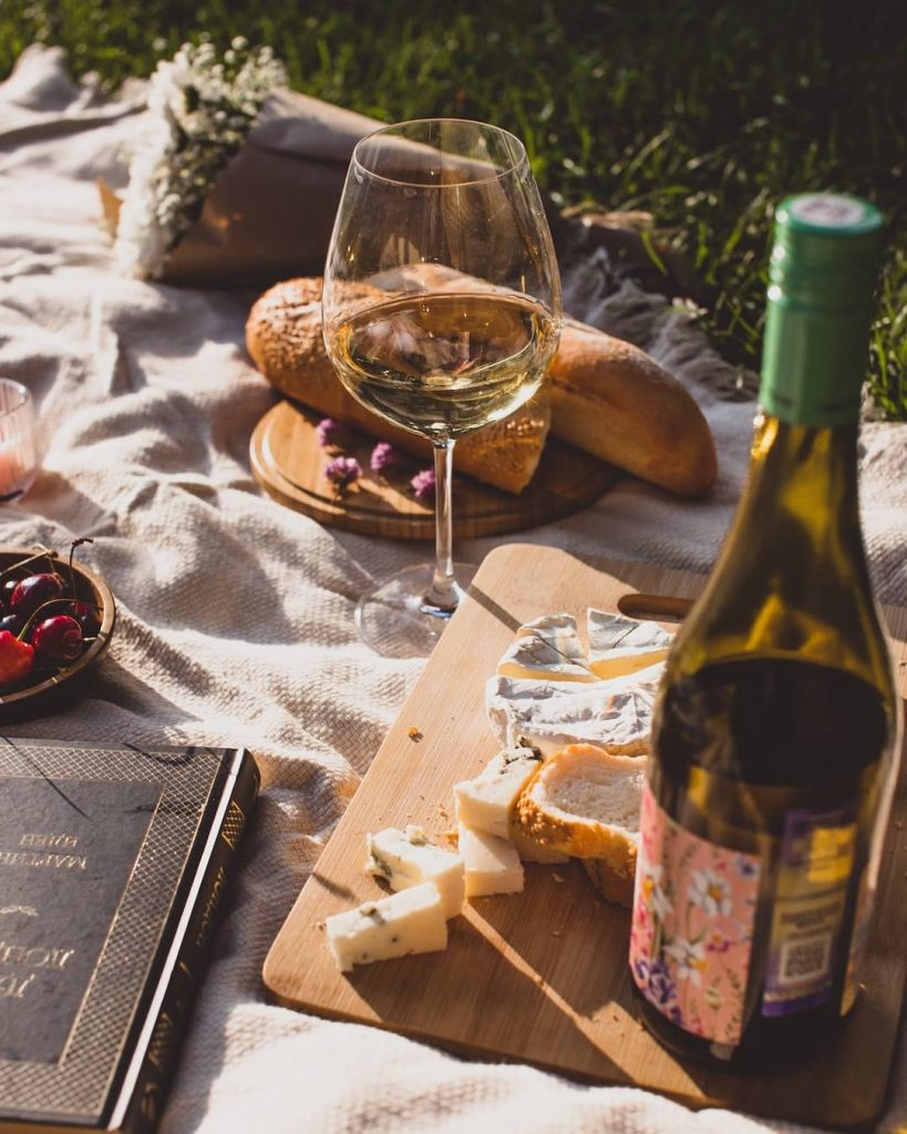 Picnic spread with wine bottle, cheese platter, and a baguette