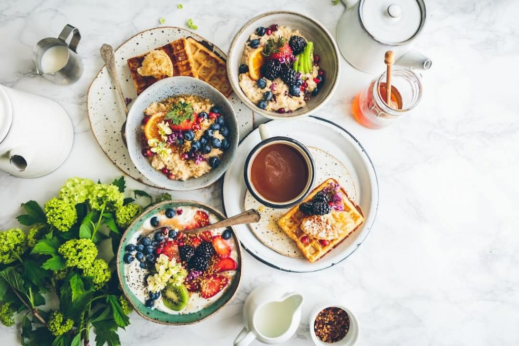 Table set with bowls of porridge, waffles, coffee cups, and flowers