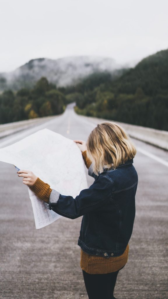 Woman standing in the middle of the road looking down at a map