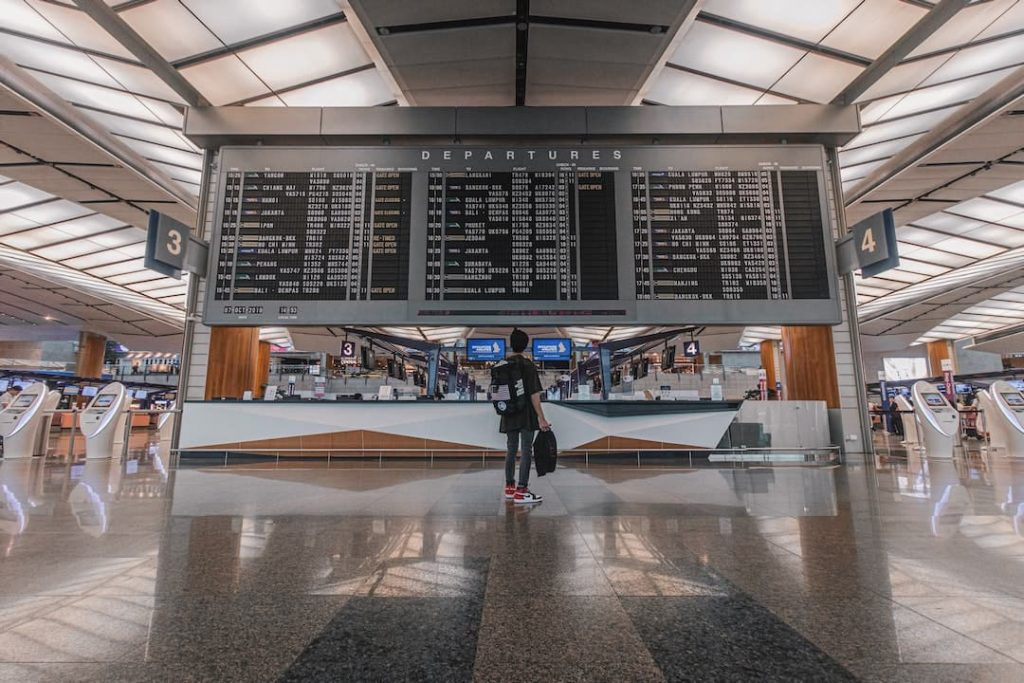 Person standing in front of departures sign in airport