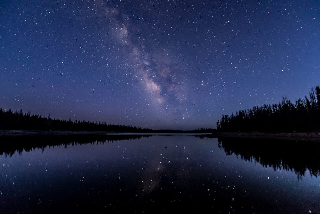 Starry sky reflecting off a lake surrounded by trees