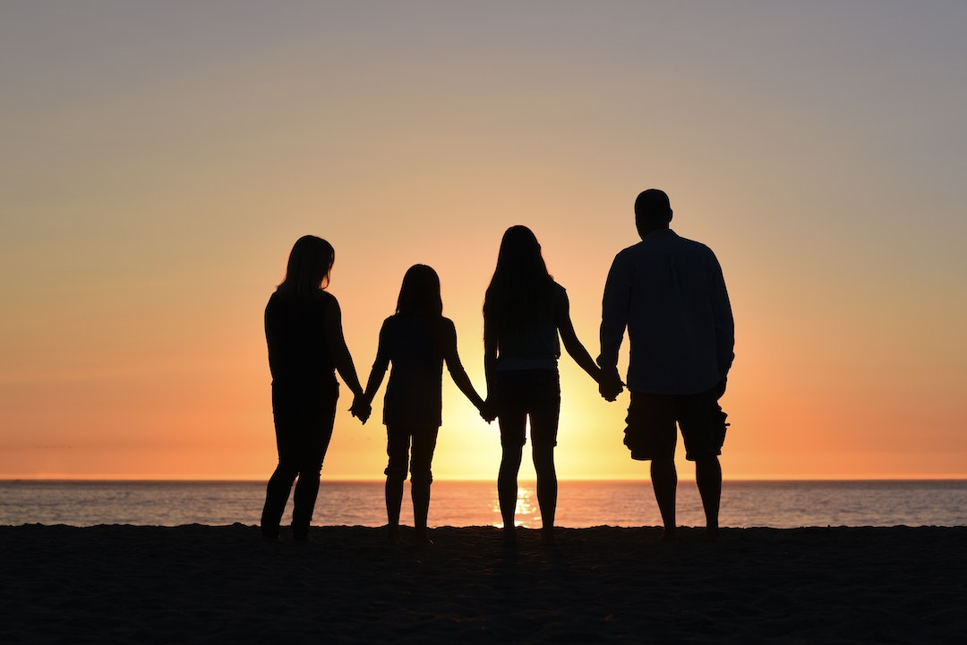 Family holding hands at the beach at sunset