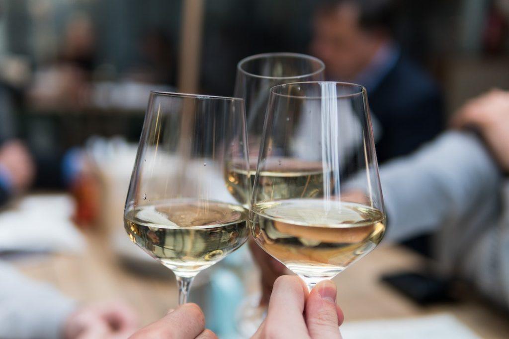 Three people cheersing with white wine
