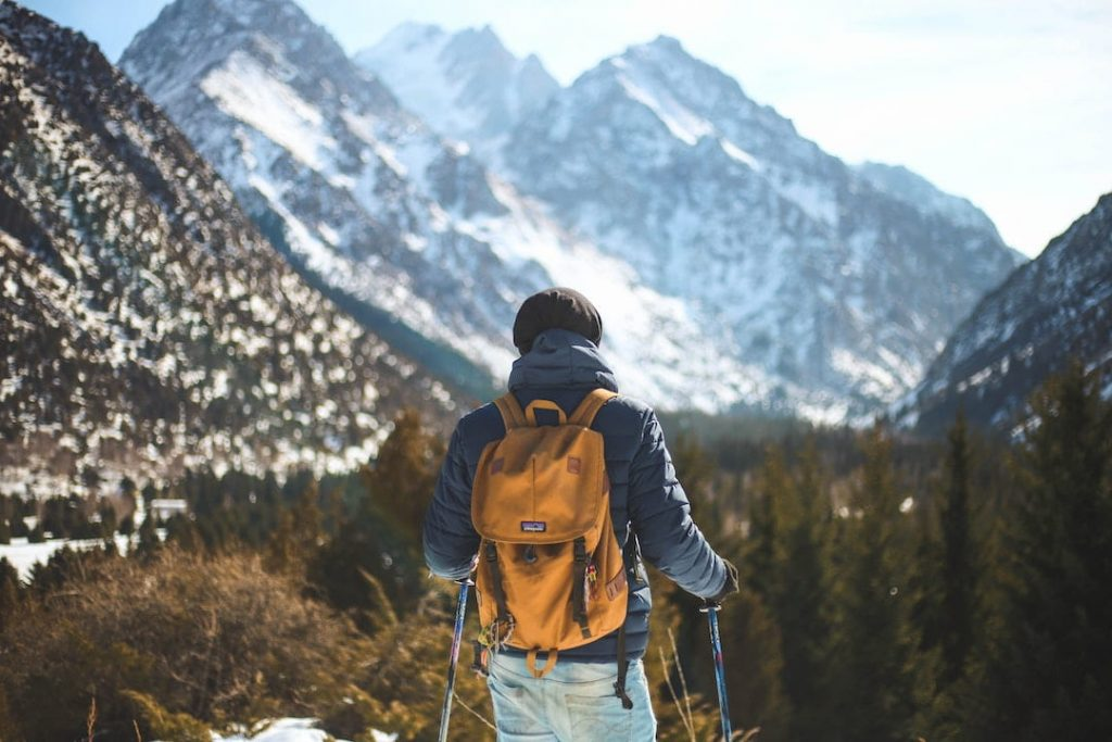 Man wearing a yellow backpack and standing in front of mountain peaks