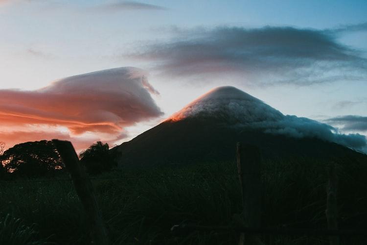 dusk falls on a volcano shrouded in cloud