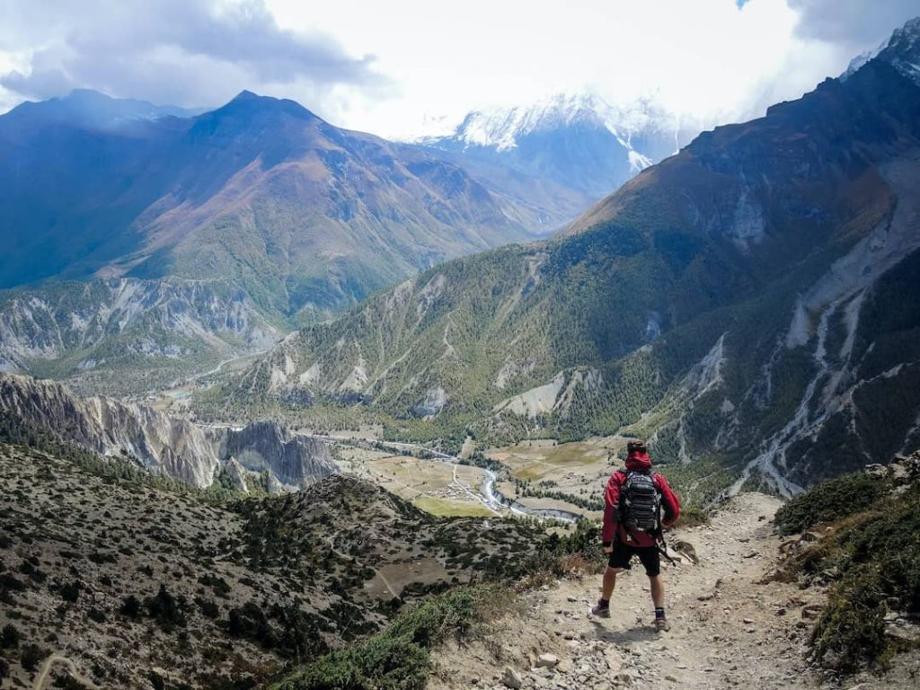 Man standing on mountain trail with peaks in the distance