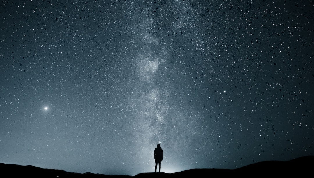 Person standing in front of a starry sky with the Milky Way in the background