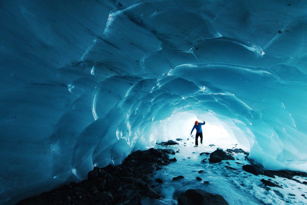 Man walking through a glacier in Alaska