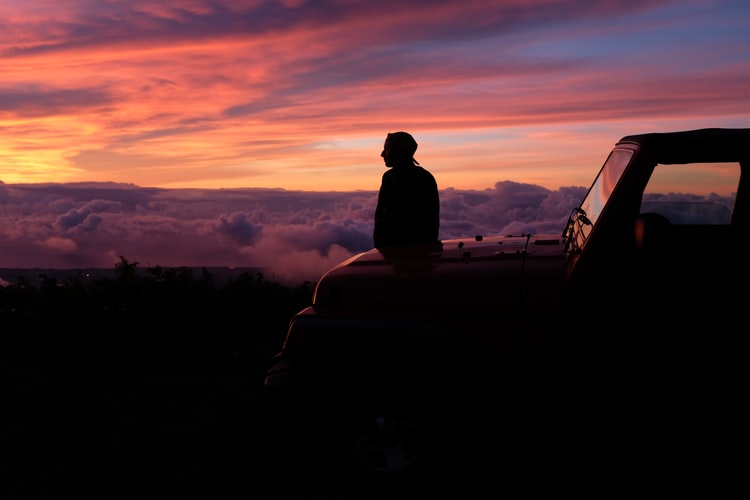 a man sitting on his bonnet overlooking a pink sunset