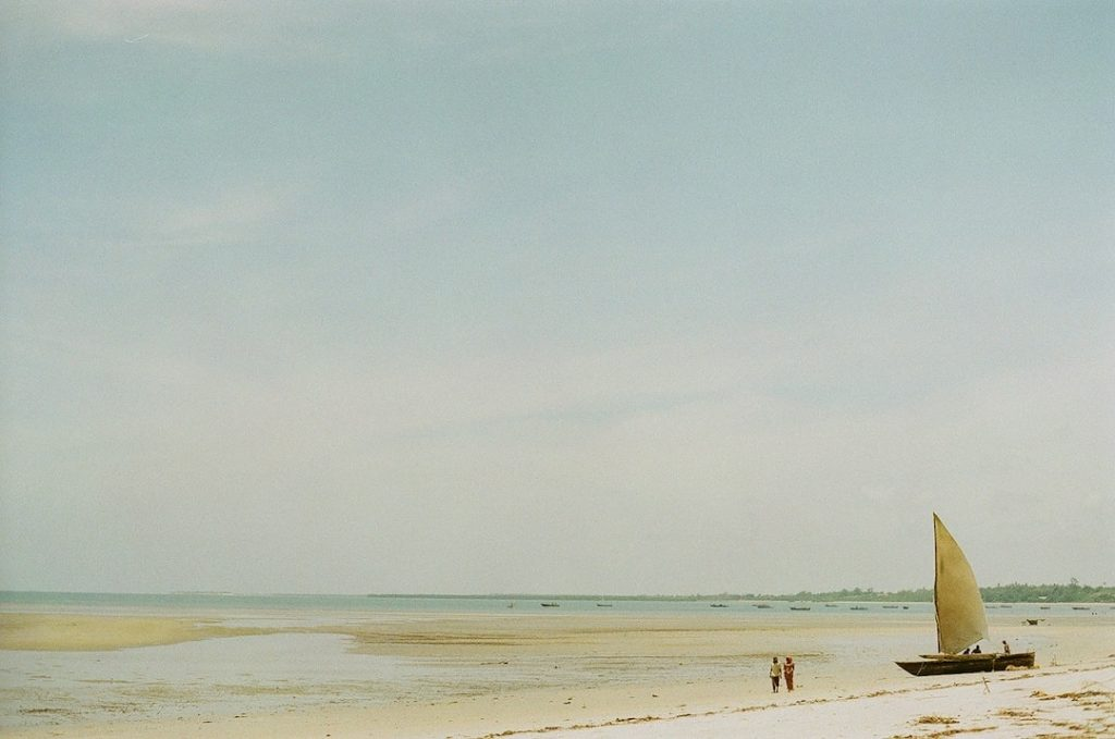 People walking on a beach beside a sailboat in East Africa
