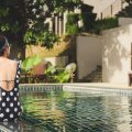 Woman sitting on the edge of a hotel pool in Thailand