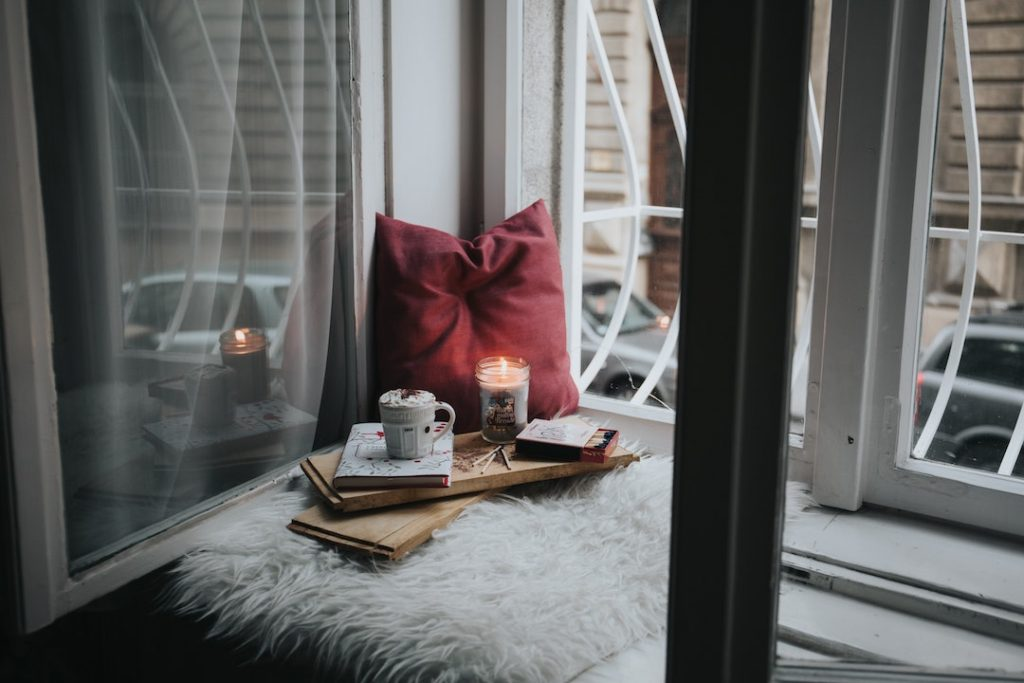 Cozy nook with a pillow and candle beside a window