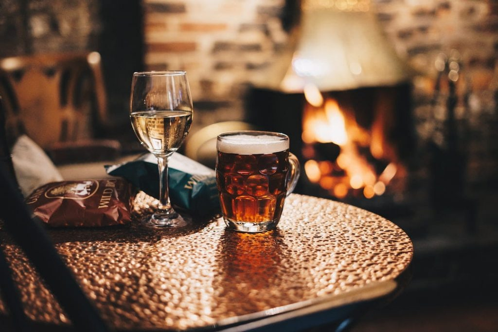 Glass of wine and mug of beer on table with a fireplace in the background