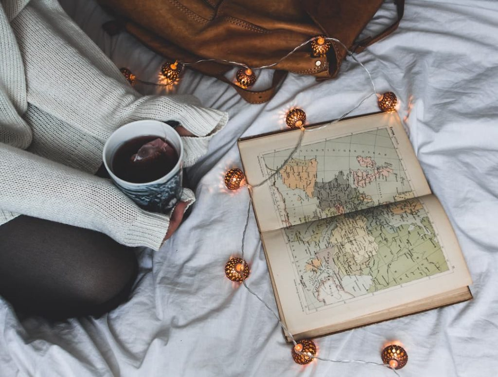 Person sitting on bed holding a cup of tea with an atlas open and fairy lights