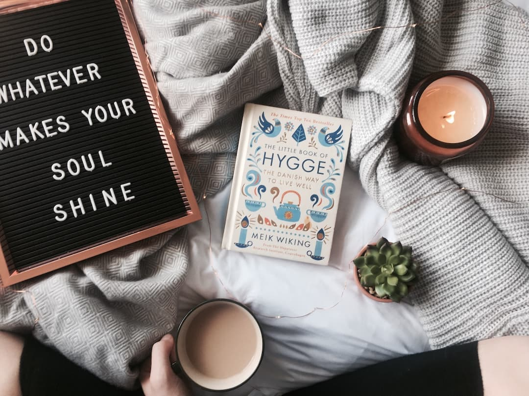 Cup of tea, candle, and hygge book on a bed