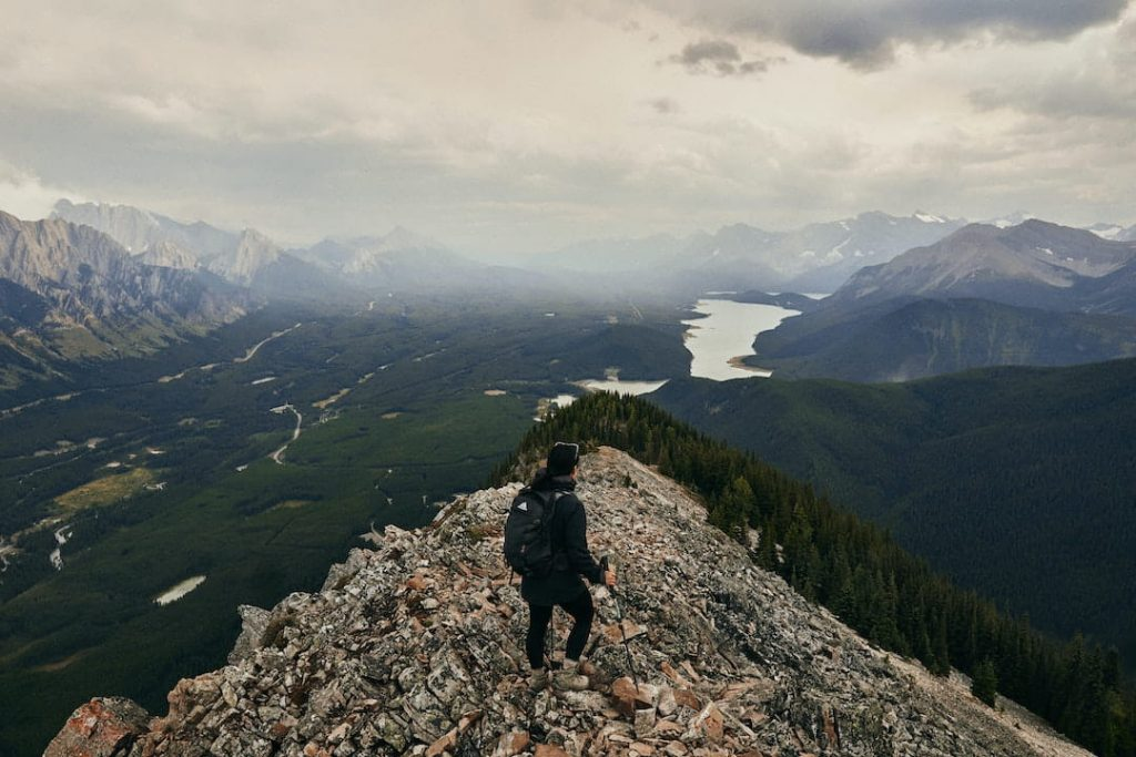 Person holding hiking poles standing at top of mountain in the Canadian Rockies