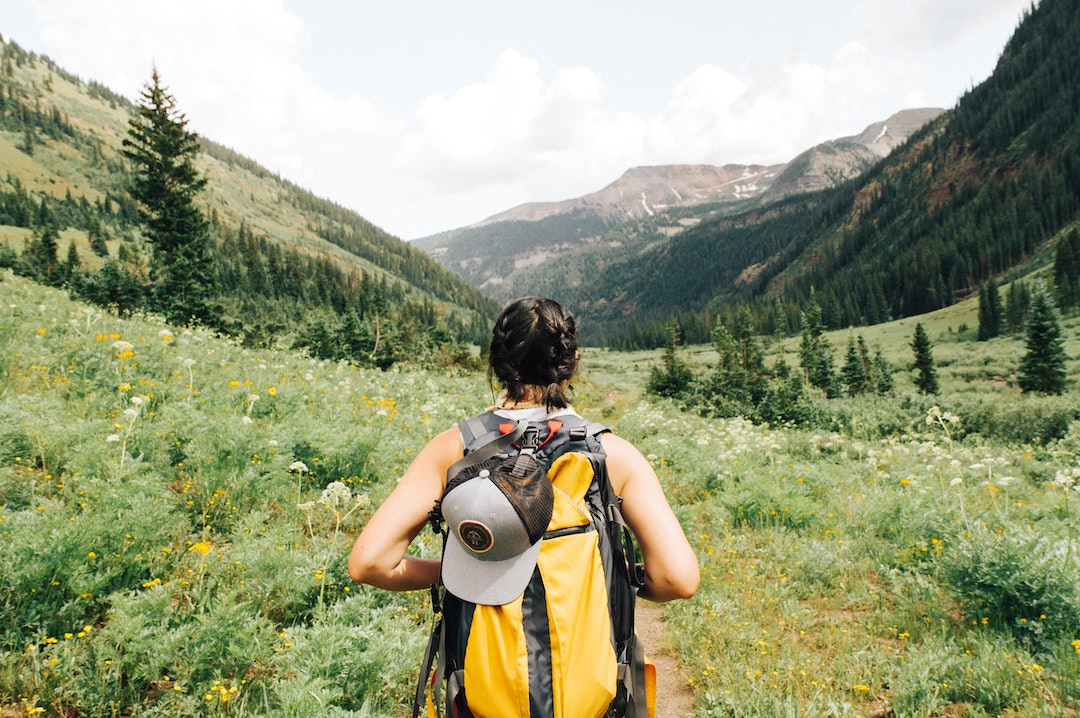 Woman with yellow backpack hiking through field with mountain peaks