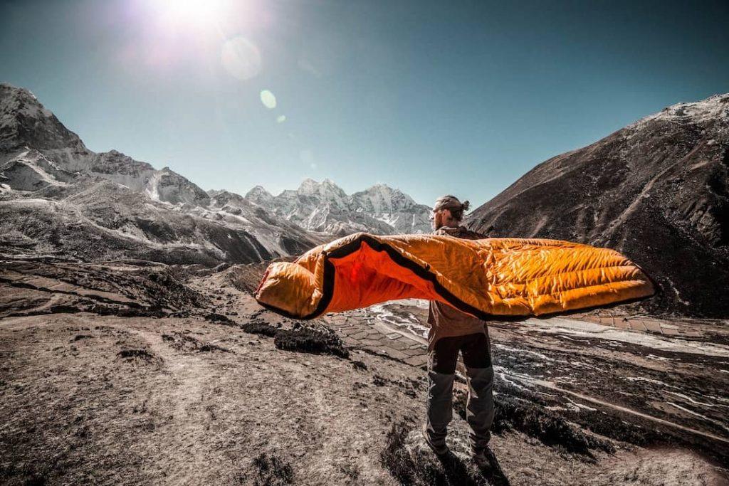Man standing on trail holding orange sleeping bag at Everest Base Camp