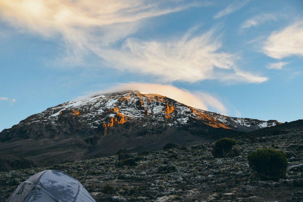 Mountain peak and tent on an open area at Kilimanjaro, Tanzania
